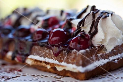 Fresh waffles with cherries, cream and chocolate