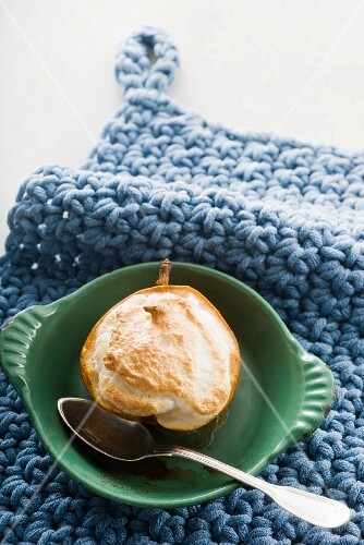 A baked pear with coconut meringue