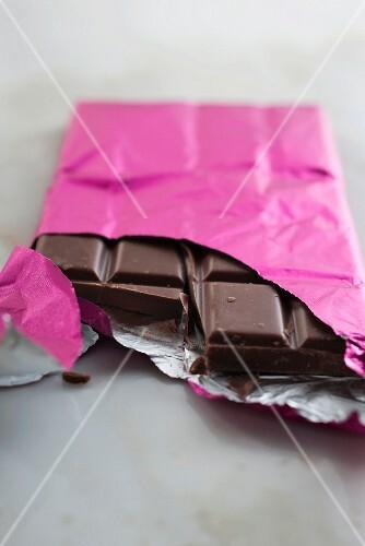 A broken chocolate bar in pink foil
