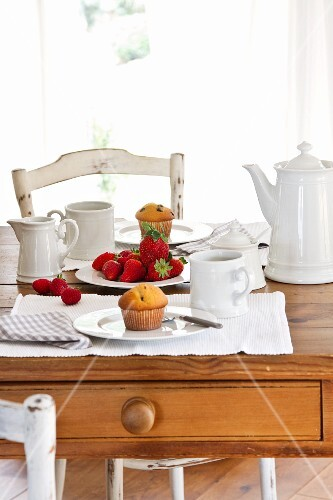 A table laid for coffee with muffins and fresh strawberries