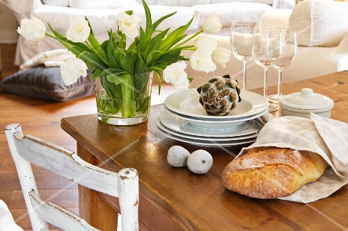 A bunch of white tulips in a glass vase next to a stack of plates, some wine glasses, decorative figs and a decorative artichoke