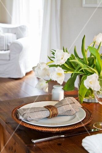 A bunch of white tulips in a glass vase; a place setting with a basket plate to the front of the image
