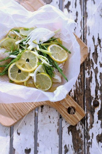 Cod with lemon slices, green beans and fennel, in grease-proof paper