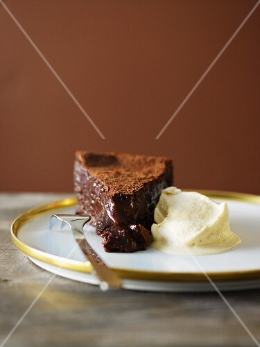A slice of chocolate cake with cocoa powder and vanilla ice cream