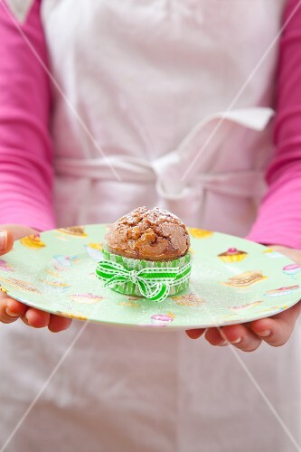 A girl holding a raspberry muffin dusted with icing sugar