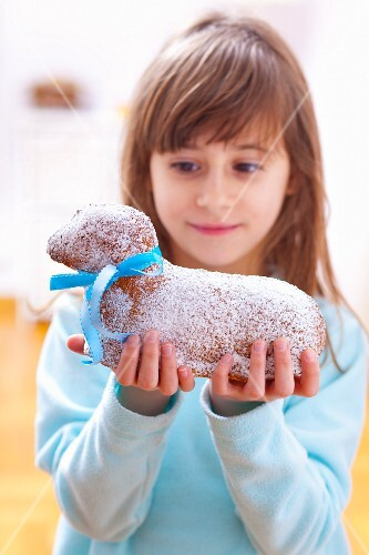 A girl holding a cake in the shape of an Easter lamb