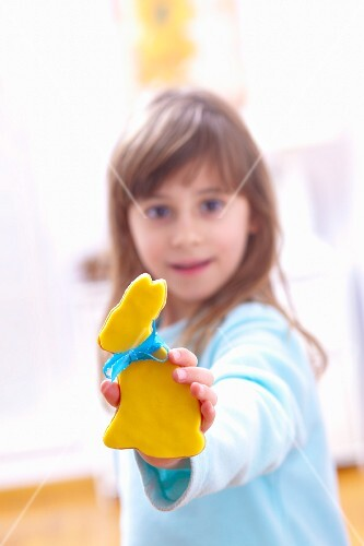 A girl holding a biscuits in the shape of an Easter bunny with yellow icing