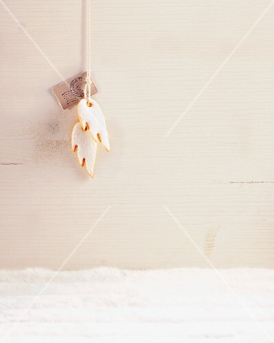 Two biscuits shaped like angel's wings, hanging from a ribbon