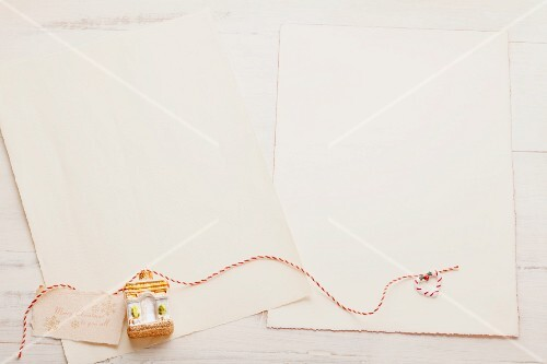 Sheets of writing paper, and a Christmas tree decoration on a narrow ribbon