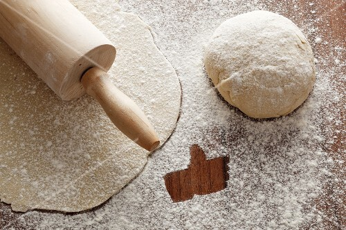 Rolled-out pastry with a rolling pin, a ball of dough, and flour with a 'like' symbol