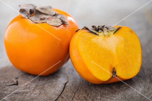 Whole persimmon and half a persimmon
