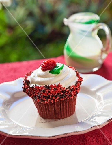 Cupcake with Vanilla Icing, Red and Chocolate Sprinkles and a Red Frosting Rose; On an Outdoor Table