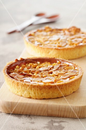Two almond tartlets on a chopping board