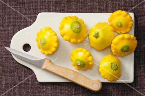 Several yellow patty pan squash on a chopping board with a knife
