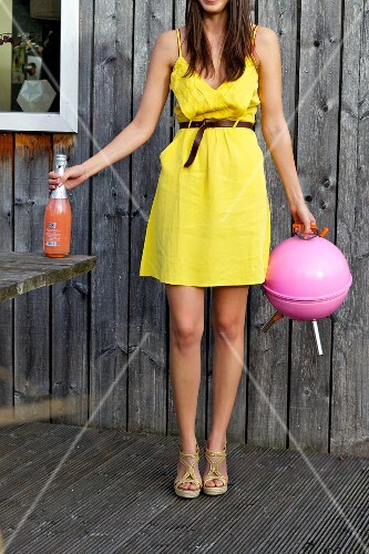A young woman in a yellow dress with a spherical pink barbecue and a bottle of Bellini