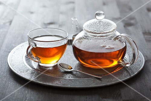 Tea in glass cup and pot