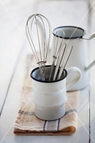 Egg whisks in an enamel mug