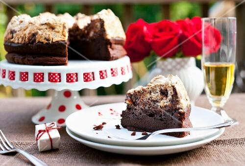 A Slice of Chocolate Hazelnut Meringue Cake on a Plate; Remainder of Cake on a Cake Plate in Background