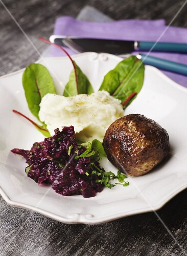 A meatball with mashed potato and red cabbage