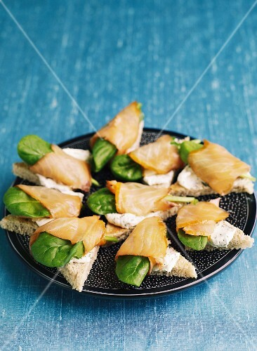 Canapés with cream cheese, smoked salmon and baby spinach