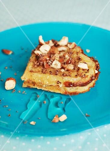 A heart-shaped waffle with hazelnuts, honey and chocolate