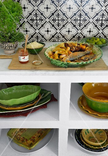 A kitchen shelf unit holding stacked ceramic crockery; on the top, a plate of oven-baked fish and vegetables and a jar of harissa sauce