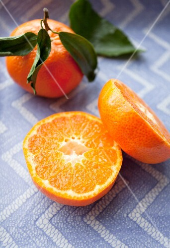 A halved mandarin and a whole mandarin with leaves