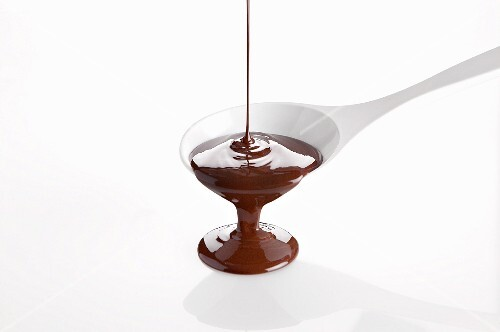 Melted chocolate pouring from a cooking spoon