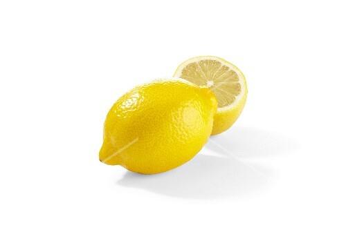 A lemon and a lemon half on a white surface