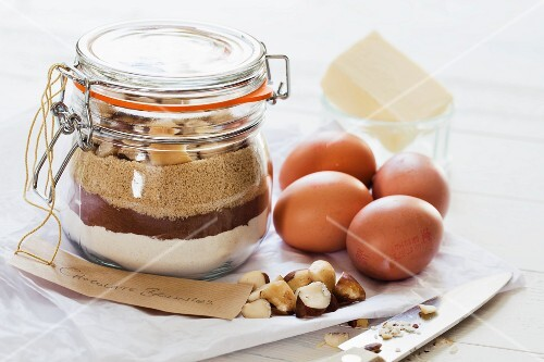 A preserving jar containing the dry ingredients for making brownies, with eggs and butter to one side