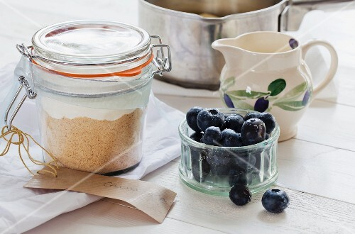 A preserving jar with dry ingredients for making cheesecake, blueberries to one side