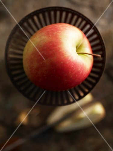 A Pink Lady apple in a dish