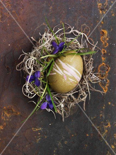 A green decorated egg for Easter in a nest