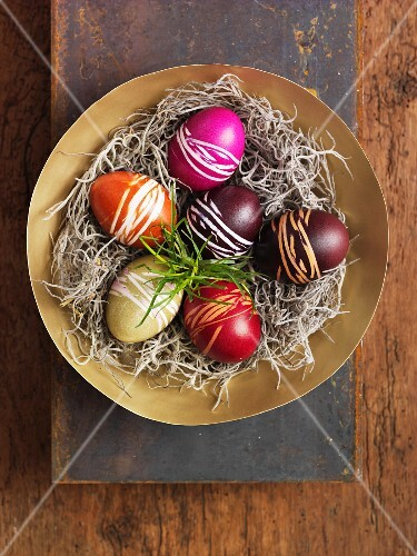 Brightly coloured eggs for Easter, in a nest (view from above)