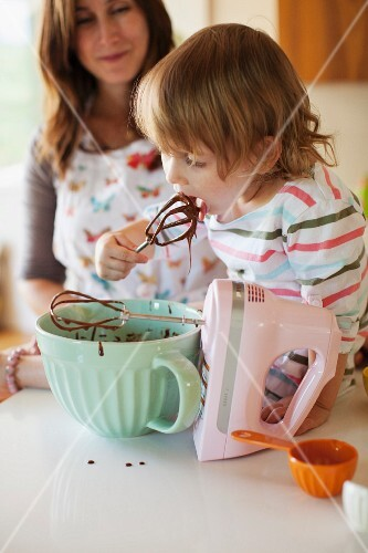 A small child licking the whisks from a hand mixer