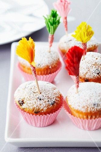 Muffins dusted with icing sugar and decorated with frilled cocktail sticks made from paper cake cases