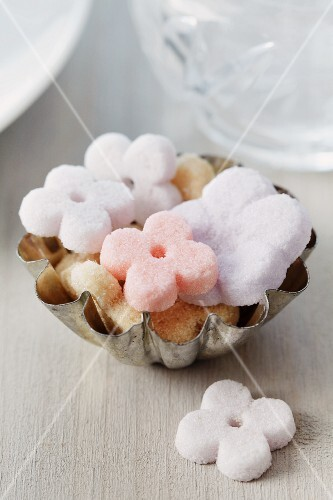 Small cake mould used as sugar bowl for flower-shaped sugar cubes
