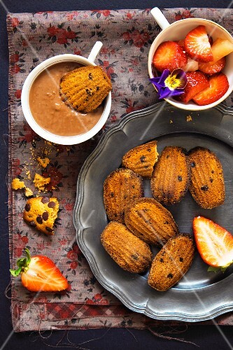 Madeleines with chocolate sauce and strawberries