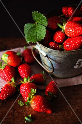 Fresh strawberries in and next to a bucket