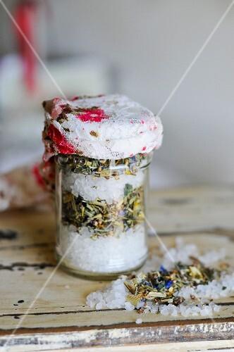 Sea salt, dried herbs and herb flowers in a preserving jar