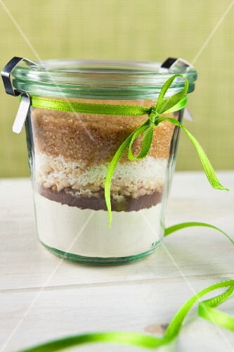 A preserving jar tied with a ribbon containing the dry ingredients for making coconut and nut biscuits