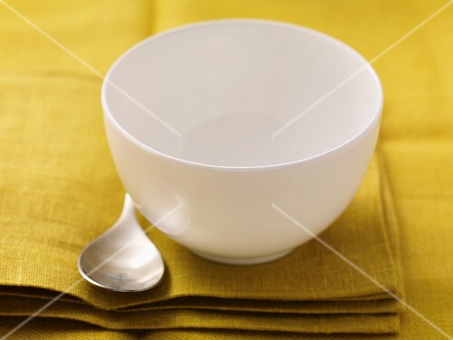 An empty soup bowl with a spoon on a napkin
