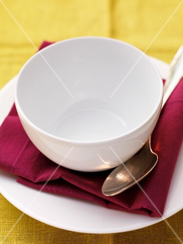 An empty bowl on a plate with a napkin and a spoon