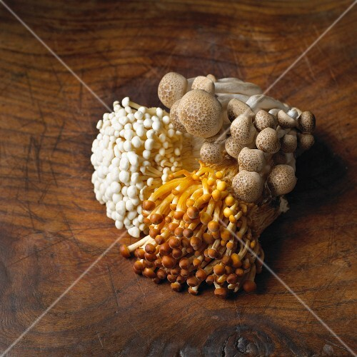 Enoki and shimeji mushrooms on a wooden surface