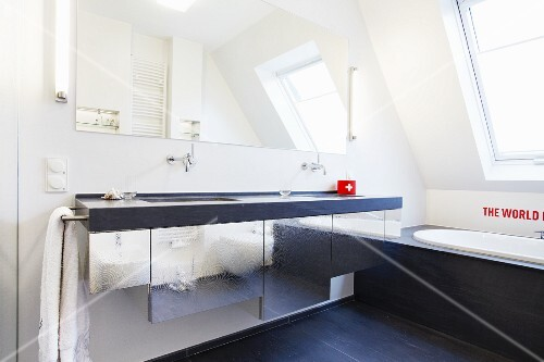 A designer bath under the roof and a generous washbasin over a cupboard with a shiny metal front
