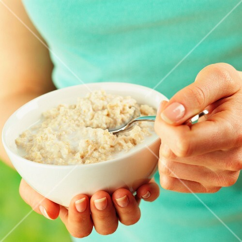 A woman holding a bowl of porridge