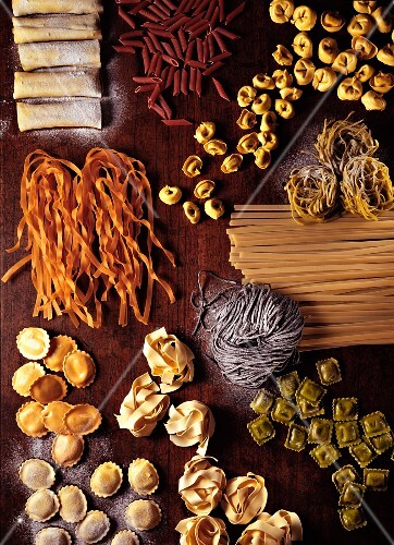 Assorted types of pasta on a wooden board