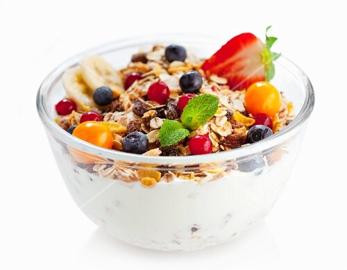 Fruit muesli with yoghurt in a glass bowl