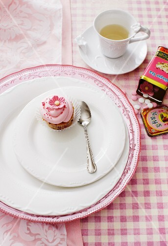 A mini cupcake on a plate with a spoon, and a cup of tea on a checked tablecloth