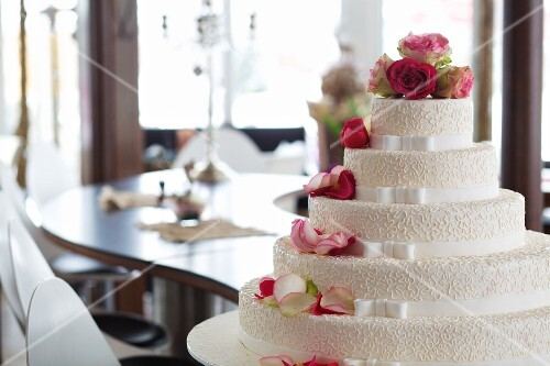 An elegant wedding cake decorated with white ribbons and pink roses